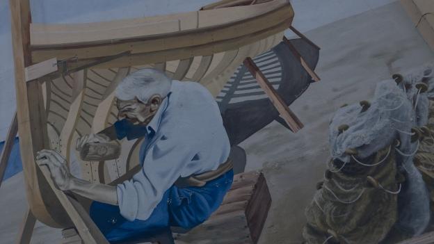 "Stintino: mural commemorating the ""maestri d'ascia"".  (Artist: Bruno Mura?)"