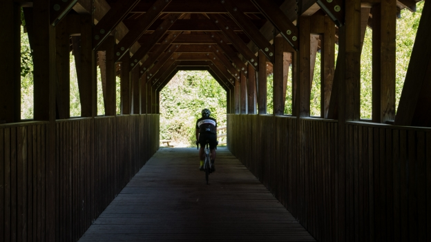 Cyclist on a wooden bridge over the Etsch near Schlanders